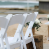 Fold-out white Americana chairs. These crisp white chairs with a padded seat are the go-to chair for weddings and events. They suit indoor and outdoor events and are foldable and stackable for ease of use.