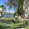 Elegant, flirtatious and fresh!  This unique Hampton's designed Wedding ceremony package comes complete with gorgeous garlands bringing an alluring, romantic style to your special day.  This is a dream Wedding ceremony package that will compliment a stunning bride on her most memorable day.  Package price includes set up and pack down.  NOTE: Package price includes faux floral arrangement on the wire mesh frame, at the registration table and also in the large Hamptons style vases. We are also able to provide fresh florals as an upgrade.